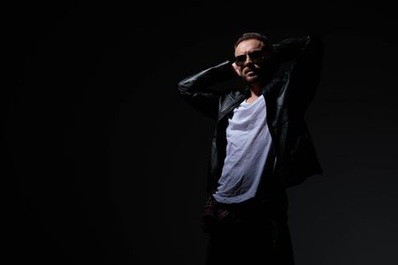 Relaxed punk man holding both hands behind his neck while wearing a leather jacket and sunglasses, standing on black studio background Stock Photo