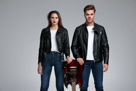 Confident rock couple leaning on an electric guitar and looking forward while both of them are wearing jeans and black leather jackets, standing on gray studio background