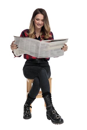 beautiful casual woman in checkered shirt and boots is sitting on a wooden chair and reading the newspaper happy on white studio background 写真素材 - 129386030