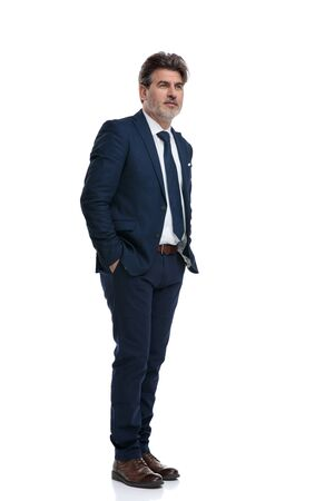 Optimistic businessman holding both hands in his pockets and hopefully looking away while wearing a blue suit and standing on white studio background 免版税图像