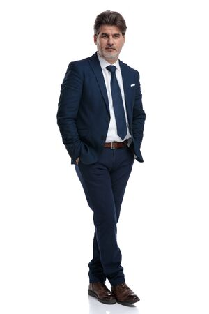 Powerful businessman standing with his legs crossed and his hands in his pockets while wearing a blue suit on white studio background Stock Photo
