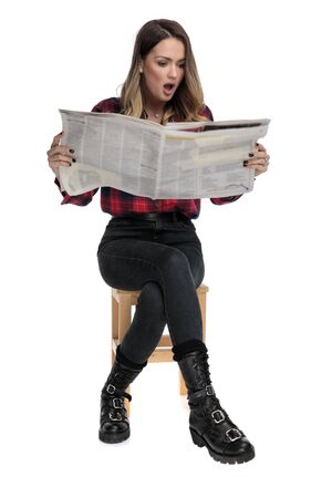 young casual woman in checkered shirt and boots is sitting on a wooden chair and reading the newspaper amazed on white studio background