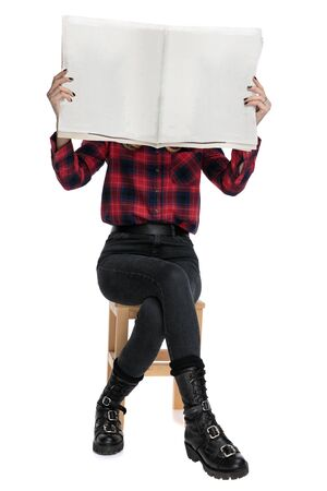 casual woman in checkered shirt and boots is sitting on a wooden chair with her face covered by a newspaper on white studio background