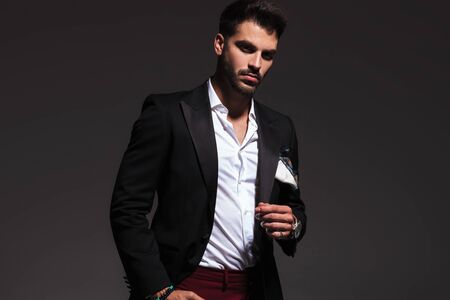 relaxed elegant man standing with hand in pocket and looks at the camera