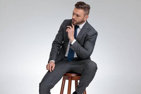 Pensativo joven empresario sentado en un taburete y se pregunta sobre algo sobre fondo gris