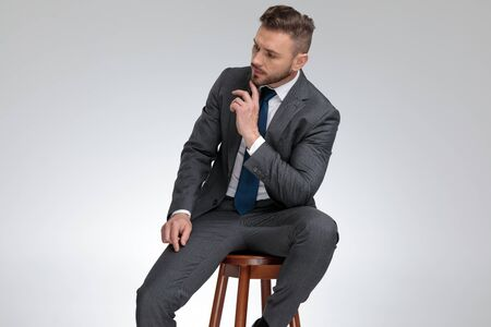 pensive young businessman sitting on stool and wonders about something on grey background