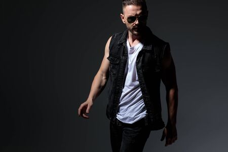 young macho man in black jeans clothes walking against dark grey background