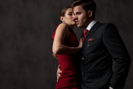 side view of a young passionate couple embracing strongly each other with a seductive look on their face on gray studio background Standard-Bild
