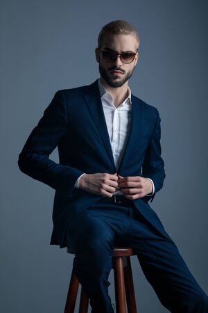 modern macho man wearing sunglasses sits and buttons his suit on grey studio background