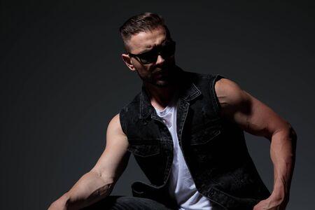 dramatic macho man wearing sunglasses looks away to side on dark studio background