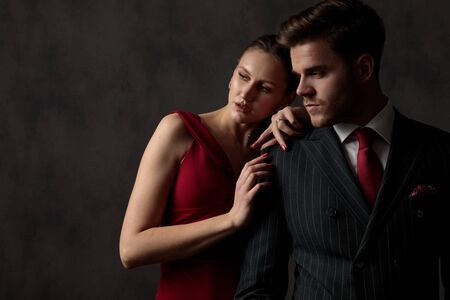 young handsome couple adorably standing side by side huged and pensively looking away on gray studio background
