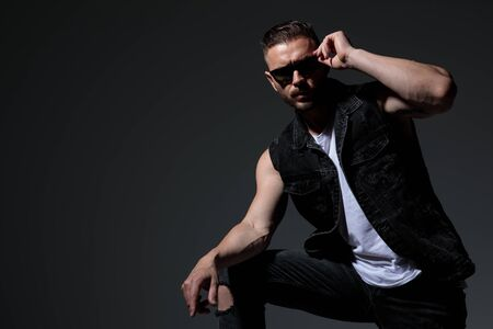 cool sexy young man put on his sunglasses and poses on dark grey background