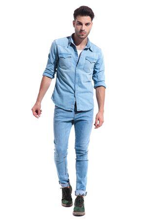 casual jonge man lopen geïsoleerd op een witte achtergrond, gekleed in een volledige denim outfit; volledig lichaam, volledige lengte Stockfoto