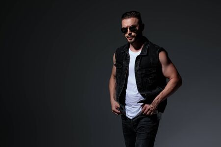 macho man wearing jeans clothes and sunglasses standing with hands in pockets on grey background 스톡 콘텐츠