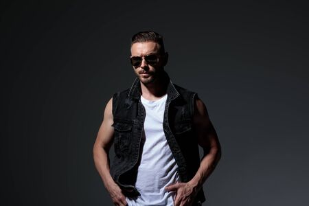 cool young fit man in jeans vest standing with hands in pockets on grey background