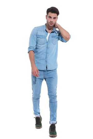 handsome young man wearing denim, touching neck, standing isolated on white background, full body, full length