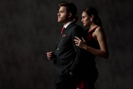 side view of a charming young couple standing and looking ahead pensively where the man has one hand in his pocket in front of his woman who holds him by his arm on gray studio background