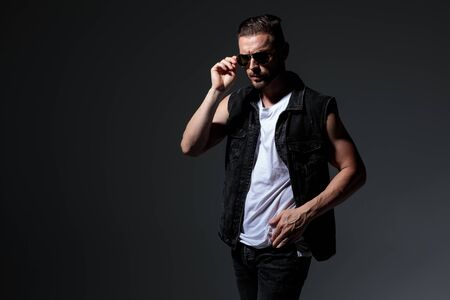 dramatic macho man puts on his sunglasses while standing on grey background 스톡 콘텐츠