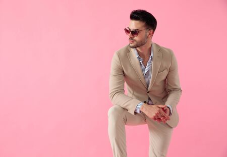 attractive young man wearing a suit and a pair of sunglasses, leaning his elbow on knee, looking to side on a pink background Banque d'images