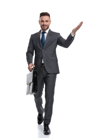 happy young businessman walking and welcoming while holding suitcase , isolated on white background