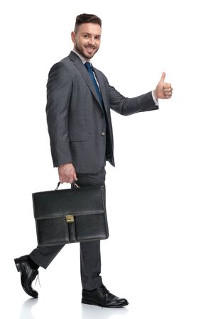 smiling young businessman walking with a suitcase and making the ok sign, isolated on white background
