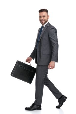 side view picture of a young man wearing suit and tie, holding a suitcase and wlks on white background