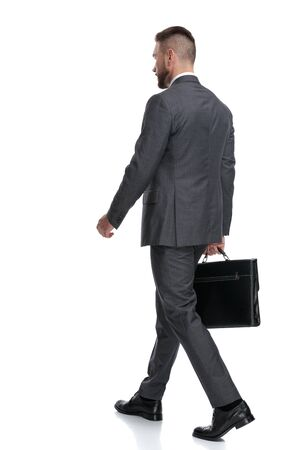 back side view of a walking businessman holding a briefcase isolated on white background Reklamní fotografie