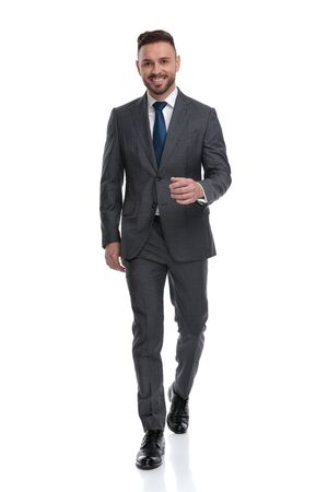 confident young businessman wearing suit and tie is walking forward , isolated on white background Stock Photo