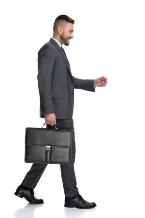 side view of a happy young businessman holding suitcase and walks, isolated on white background