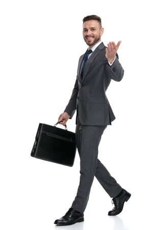happy young businessman is walking and welcoming while holding briefcase, isolated on white background