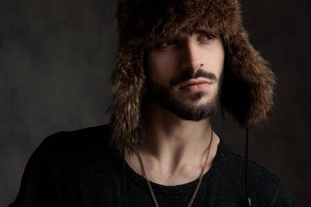 attractive casual man wearing a fur hat, looking to side, standing isolated on grey background, portrait