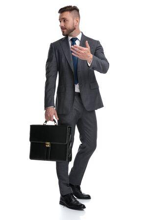 Jonge manager legt iets uit aan iemand achter zijn rug, gebaren en praten, geïsoleerd op een witte achtergrond Stockfoto