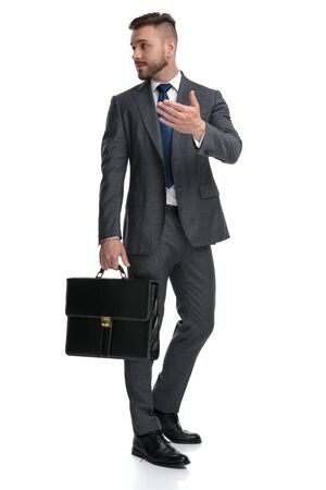 junger Manager, der jemandem hinter seinem Rücken etwas erklärt, gestikuliert und spricht, isoliert auf weißem Hintergrund Standard-Bild