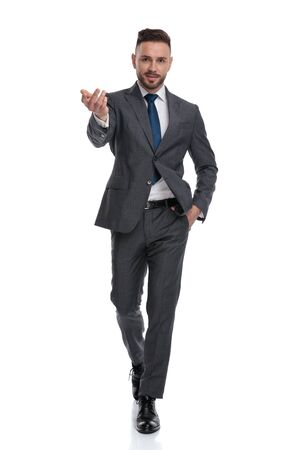 smiling young businessman walks and welcomes with on hand in pocket, isolated on white background