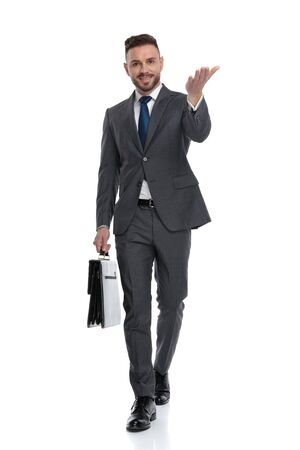 happy young businessman holding briefcase is walking and inviting, isolated on white background