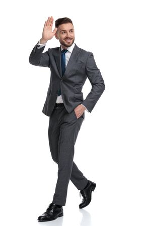 smiling young businessman calls and greets someone while walking isolated on white background