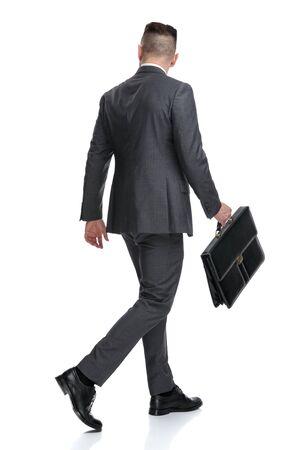 Vista posterior de un joven empresario caminando y mirando a un lado mientras sostiene la maleta, aislado sobre fondo blanco.