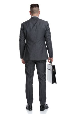 back view of a young businessman holding suitcase and looks away, isolated on white background