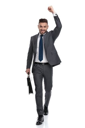 ecstatic young businessman walking with suitcase and celebrates success isolated on white background