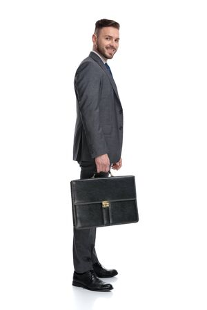 smiling young businessman holding suitcase is waiting in line, isolated on white background, side vie picture