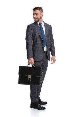 Der lächelnde junge Geschäftsmann mit Aktentasche blickt über die Schulter auf etwas auf weißem Hintergrund zurück