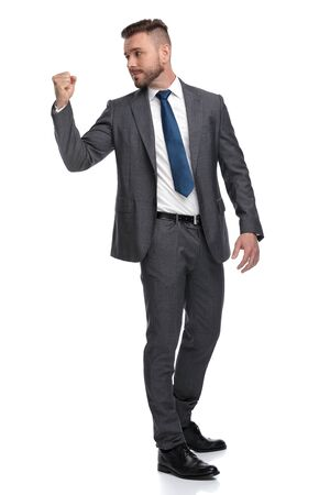 young business man threatens to fight with people at his back, isolated on white background Banco de Imagens