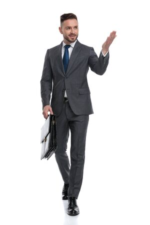 young walking businessman holding briefcase is presenting something to side, isolated on white background