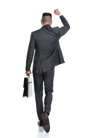back view of a winning businessman celebrating success with one hand in the air, isolated on white background
