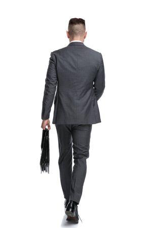 Vista posterior de un joven empresario caminando hacia adelante aislado sobre fondo blanco.