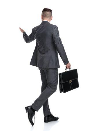 Rückansicht eines gehenden Geschäftsmannes, der präsentiert oder begrüßt, isoliert auf weißem Hintergrund