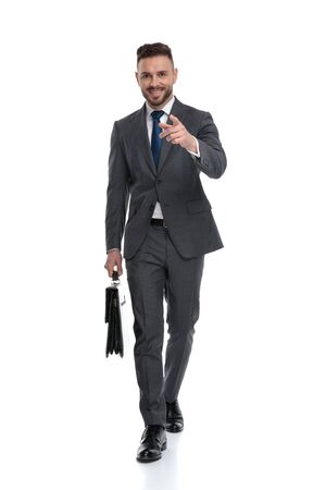 walking young smiling businessman is pointing finger forward, isolated on white background