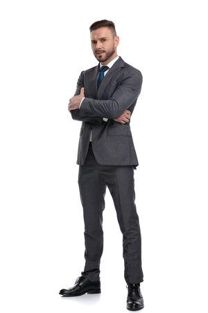 Confiado joven hombre de negocios de pie con las manos cruzadas, aislado sobre fondo blanco.