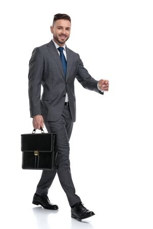 confident and happy young businessman is walking with his briefcase, side view isolated on white background