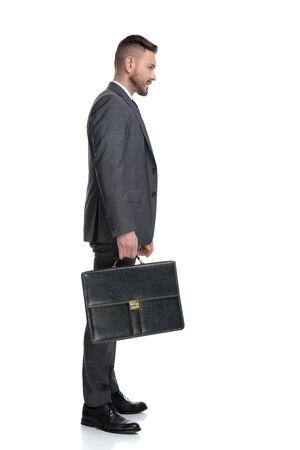Seitenansicht eines selbstbewussten jungen Geschäftsmannes, der Koffer hält und wegschaut, isoliert auf weißem Hintergrund